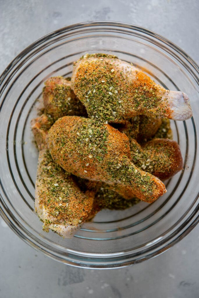 glass bowl filled with chicken drumsticks topped with seasoning