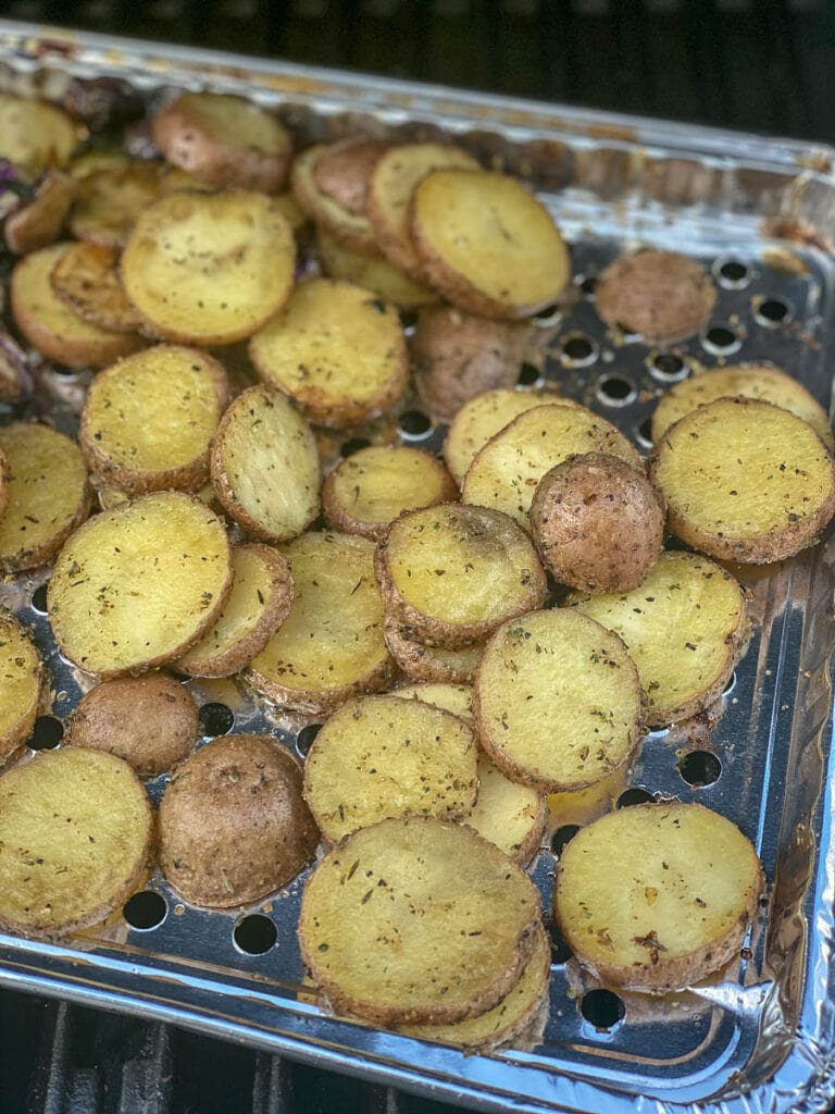 sliced potatoes with seasoning on a grill tray