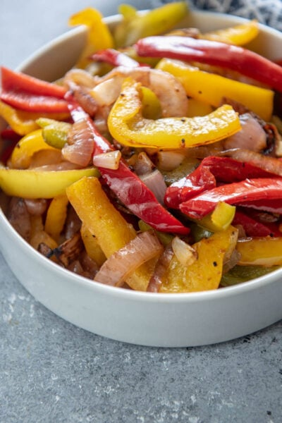 white bowl filled with grilled peppers and onions with fajita seasoning