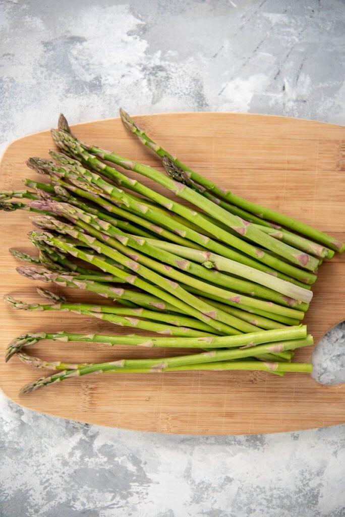 bundle of raw asparagus on a cutting board