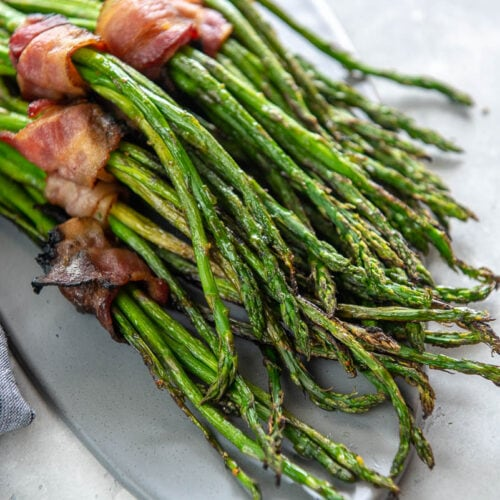 gray platter topped with grilled asparagus bundles wrapped in bacon