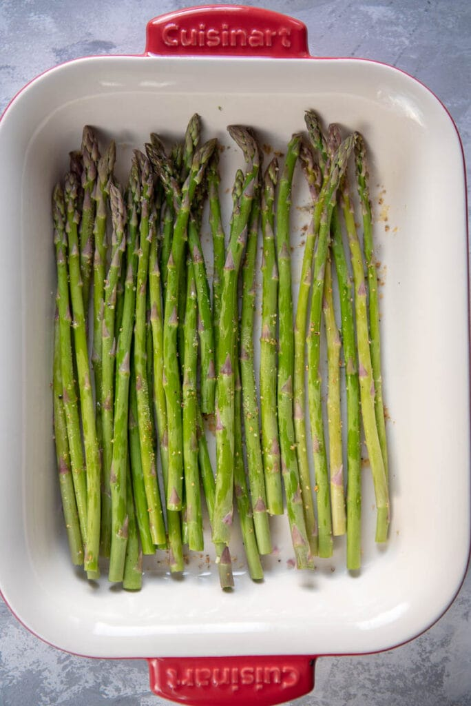square casserole dish filled with raw seasoned asparagus
