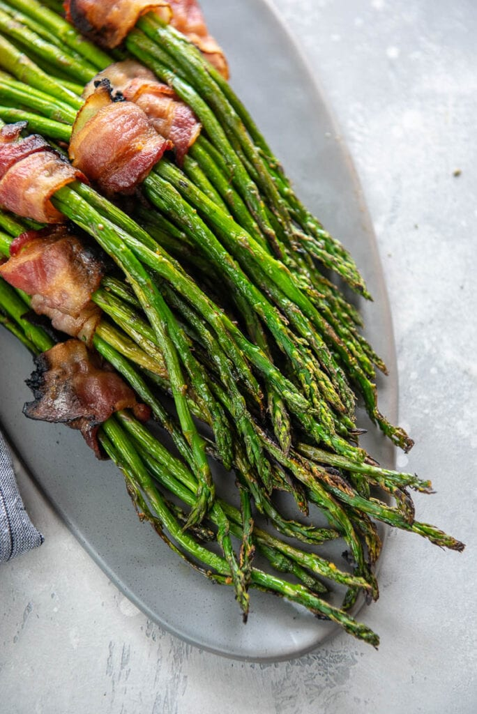 bacon wrapped grilled asparagus bundles on a gray platter