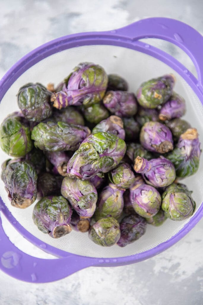 purple handles strainer filled with purple Brussels sprouts