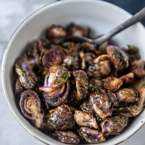 purple grilled Brussels sprouts in a white bowl with a gold rim