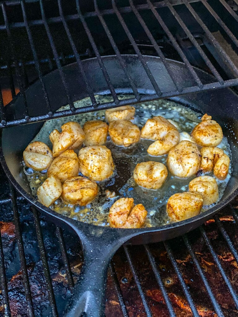 cast iron skillet on the grilled with with scallops cooking in melted butter