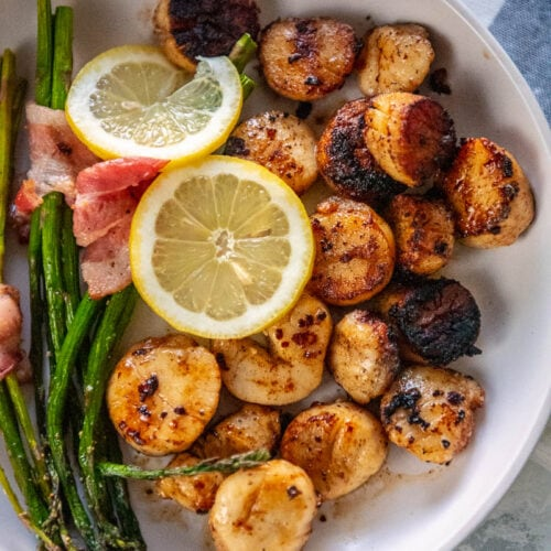 overhead shot of white bowl with grilled scallops on one side and bacon wrapped asparagus on the other