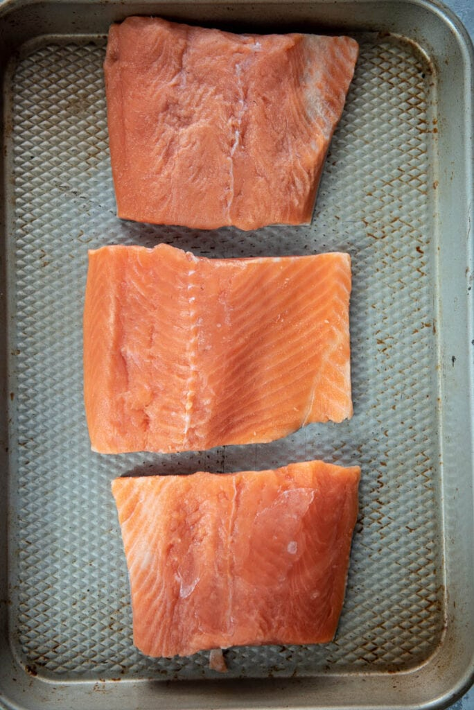 three pieces of raw salmon on a cookie sheet