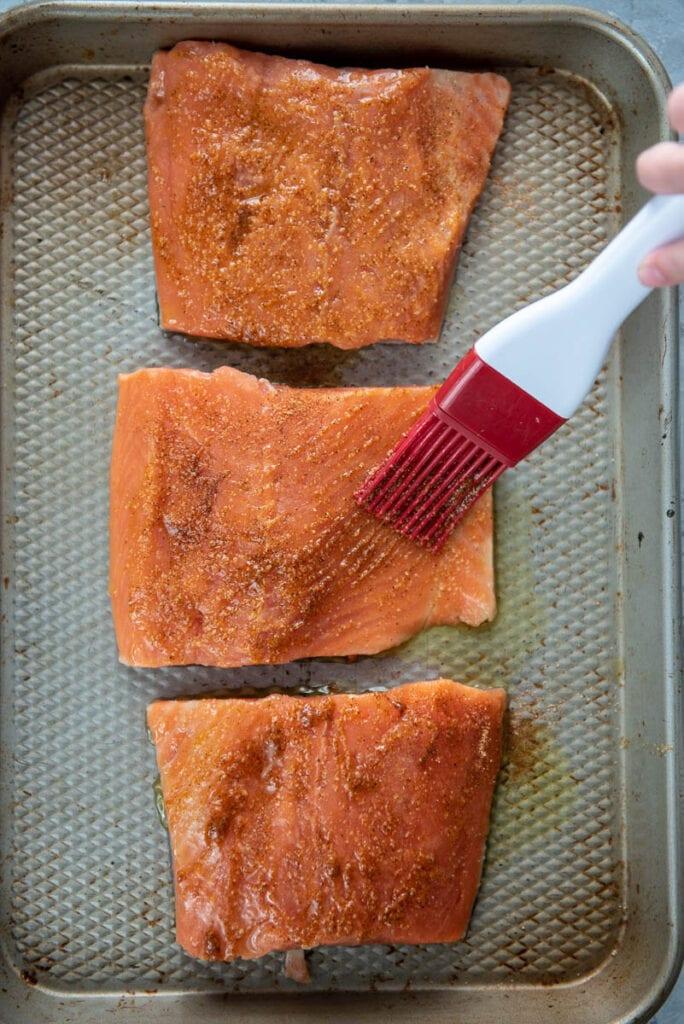 brushing oil and seasoning on raw salmon using a brush