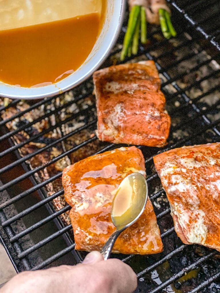 spooning sauce over salmon on grill