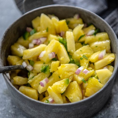 gray metal bowl filled with pineapple salsa