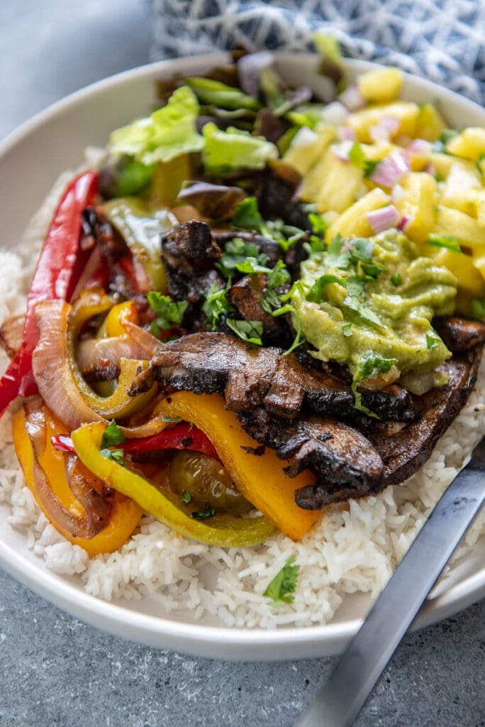 grilled mushrooms on bed of rice in white bowl topped with peppers and guacamole