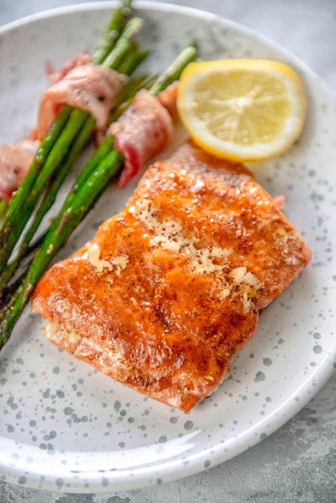 orange glazed salmon fillet on plate with asparagus and lemon