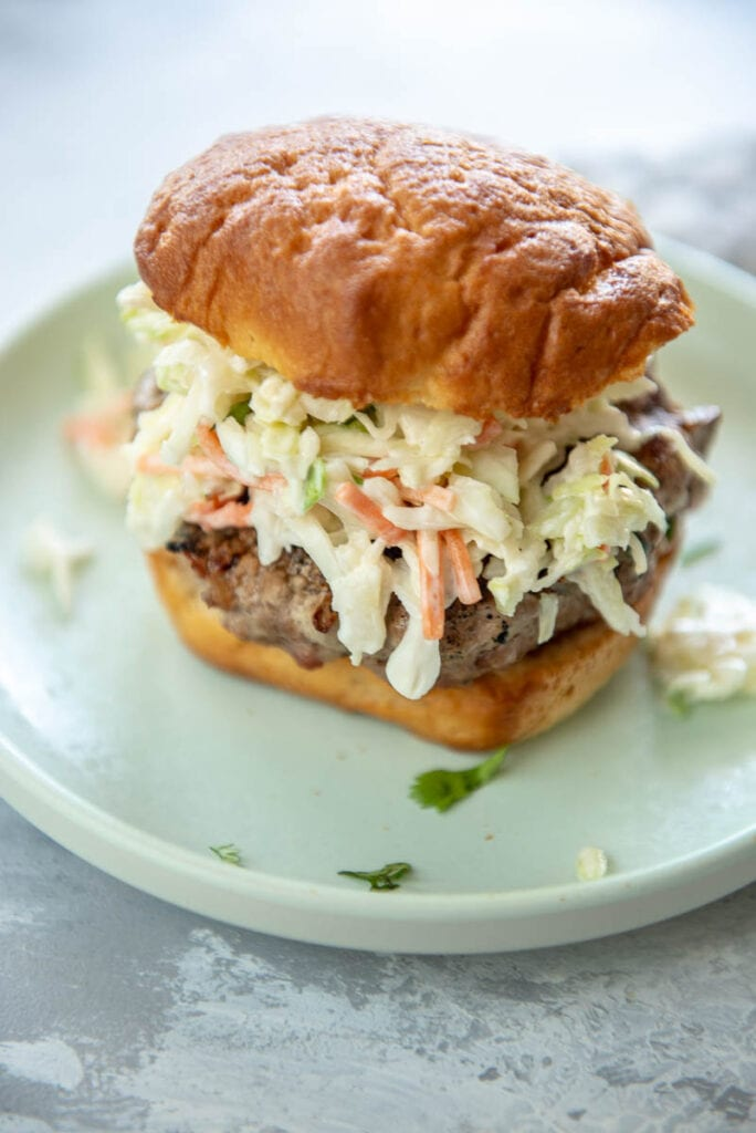 side view of pork burgers on gluten free bun topped with coleslaw on a green plate