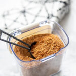 plastic seasoning container with taco seasoning and black tablespoon