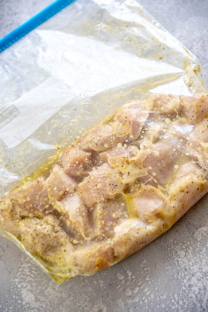 cut up chicken with marinade in plastic zipper bag