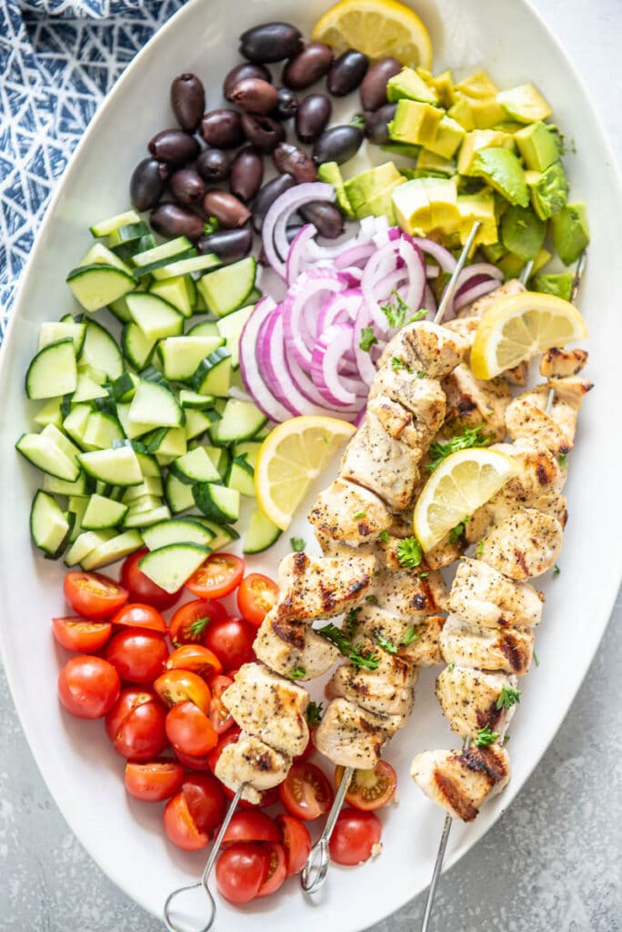 oval platter filled with chicken kabobs, tomatoes, cucumbers, olives and onions