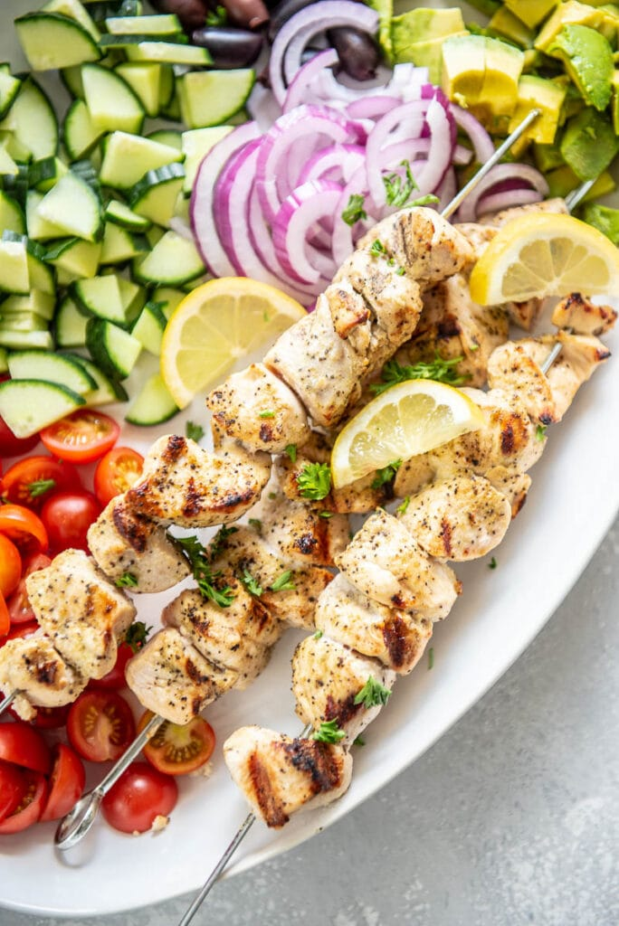chicken skewers over a platter of fresh veggies
