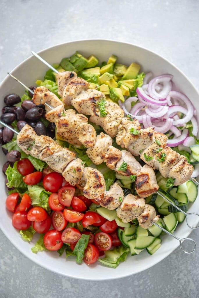 chicken skewers over greek salad ingredients in a white bowl