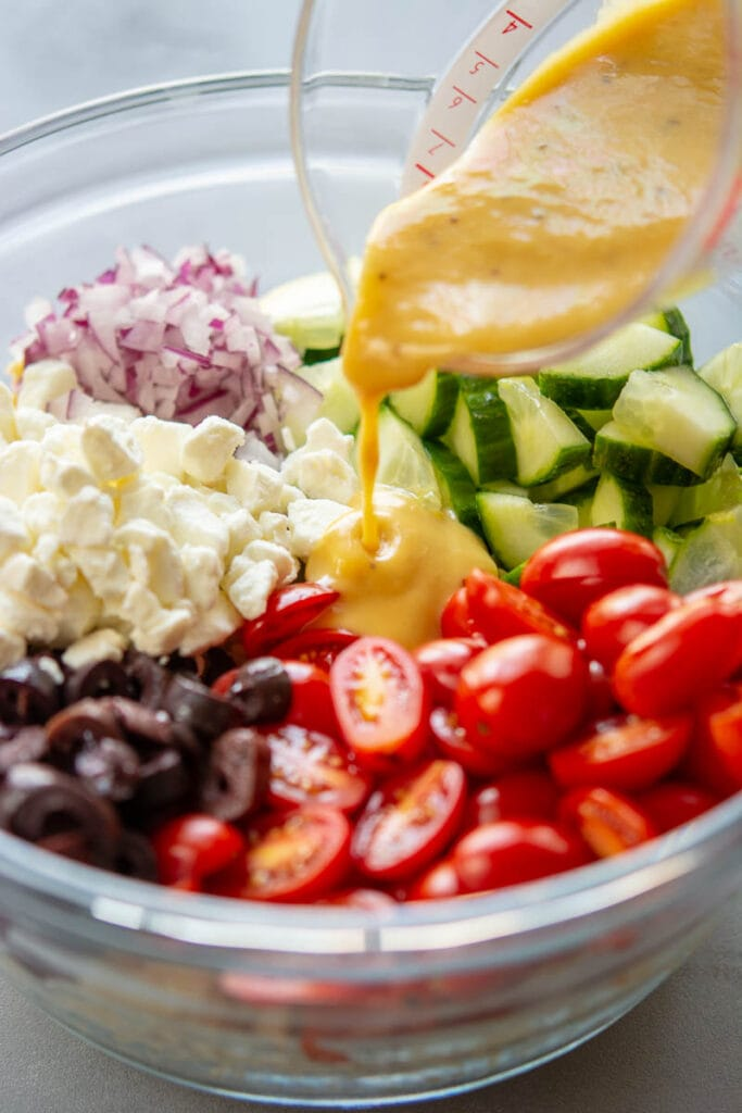 dressing poured on greek orzo salad ingredients