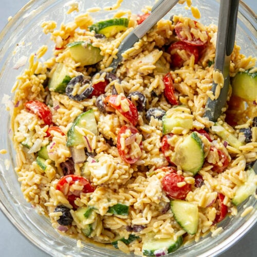 tongs mixing greek orzo salad