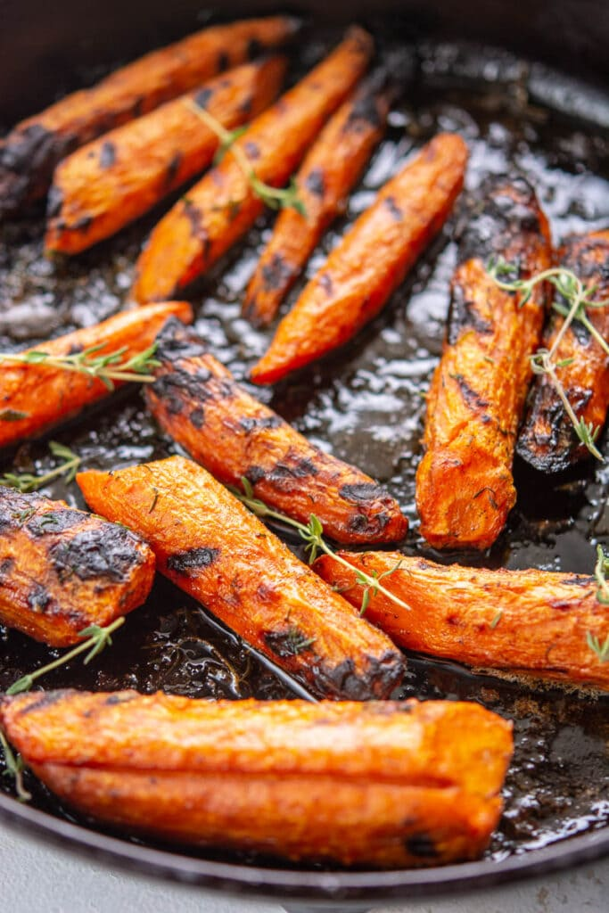 closeup of carrots and seasonings in a grill pan