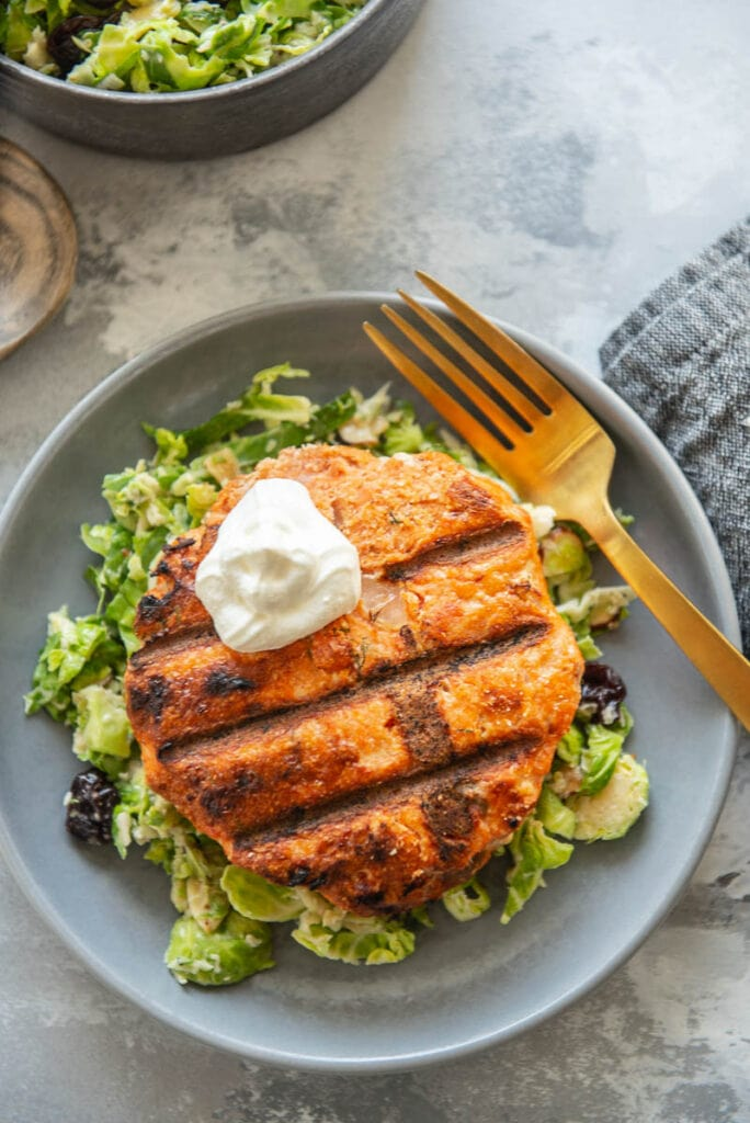 grilled salmon burgers on a plate with a fork