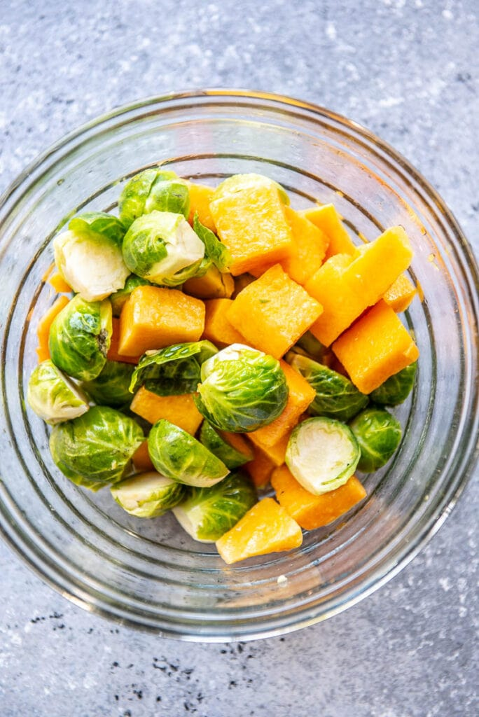 brussels sprouts and cubed butternut squash in a glass bowl