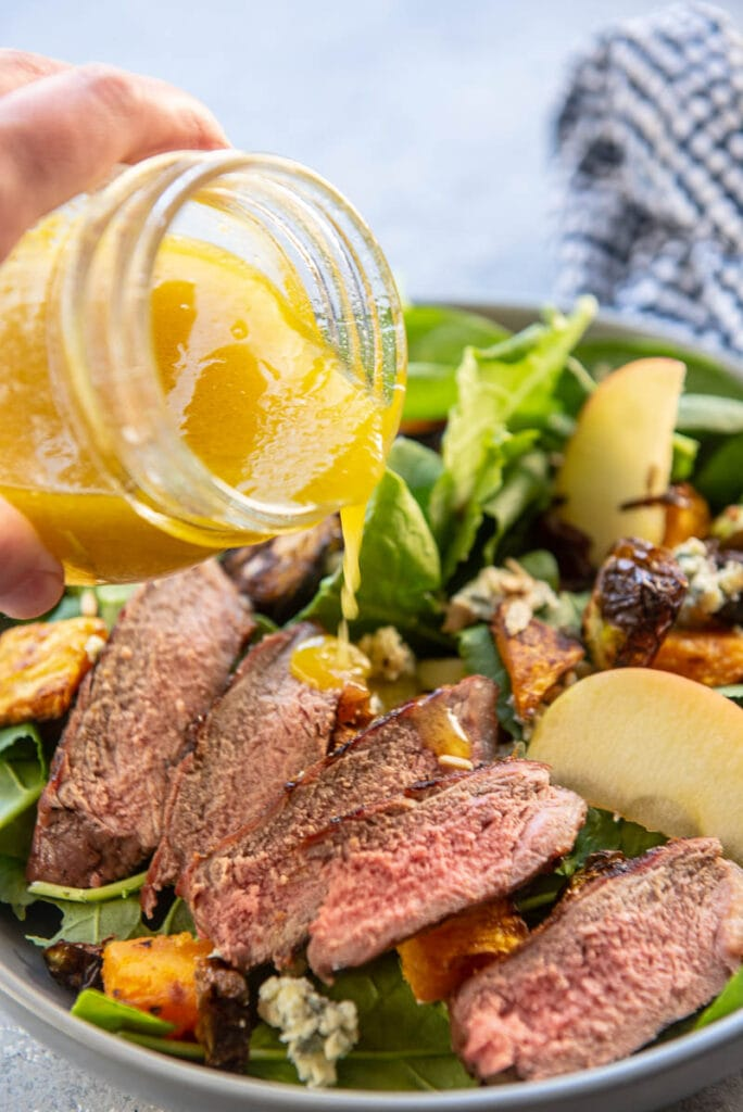 fall steak salad with apple cider vinaigrette poured on