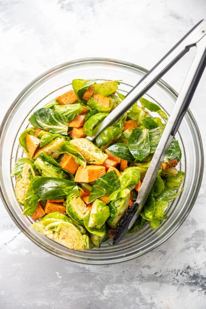 chopped sweet potatoes and brussels sprouts with seasonings in bowl with tongs