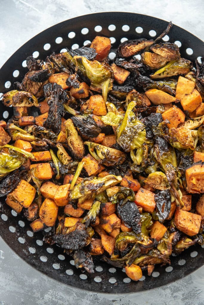 sweet potatoes and brussels sprouts in a grill basket